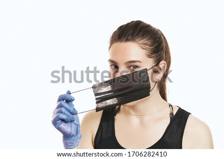 A close-up portrait of a pretty female wearing a surgical mask isolated on a white background Royalty-Free Stock Photo #1706282410