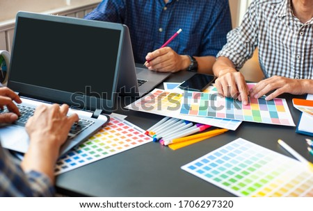 Team of professional designers work together at the office desk. Royalty-Free Stock Photo #1706297320