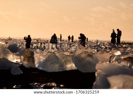 Silhouettes of tourists as they take pictures of Icebergs on Diamond Beach in Iceland as the sun sets