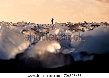 Silhouette of a tourist taking a picture of Icebergs on Diamond Beach in Iceland as the sun sets