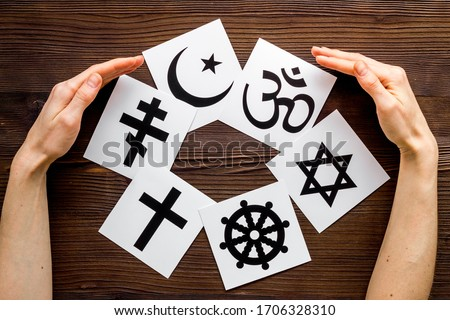 World religions concept. Hands hugs Christianity, Catholicism, Buddhism, Judaism, Islam symbols on wooden background top view Royalty-Free Stock Photo #1706328310