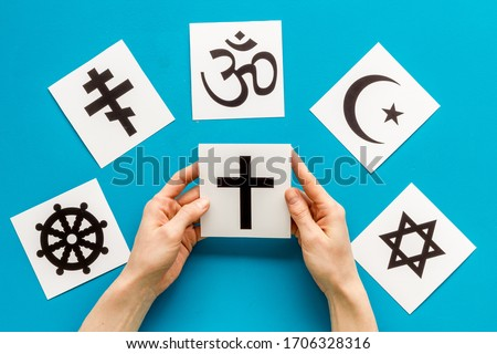Choose religion concept. Hand with catholic cross near world religions symbols on blue background top view Royalty-Free Stock Photo #1706328316
