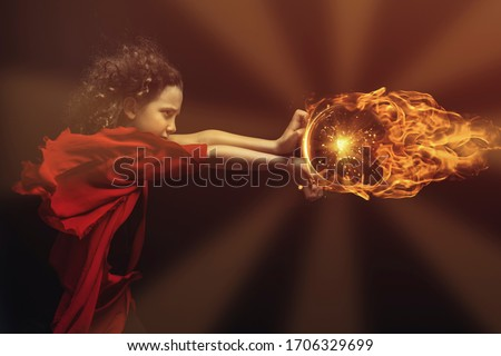 Young boy in red and black costume, wind blowing in his curly hair Royalty-Free Stock Photo #1706329699