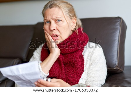 Senior woman sitting at a table in her living room reading the information sheet of her prescribed medicine #1706338372