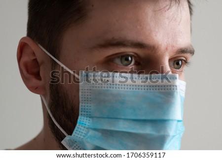 Close Up Shot of Young  Man Looking Camera Wear Surgical Mask With Gray Background #1706359117