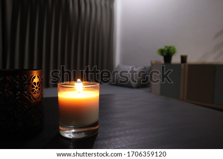 The luxury lighting aromatic scent clear color glass candle is displayed in the minimal design bedroom Royalty-Free Stock Photo #1706359120