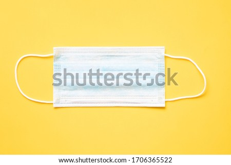 a disposable sergical mask, layed flat on yellow background
