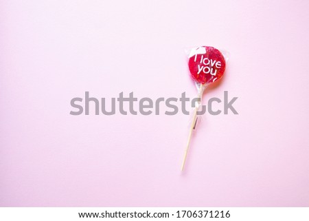 "a sweet wrapped ""I Love you"" red lollypop against a pastel yellow background, flat lay, top view, minimalistic"