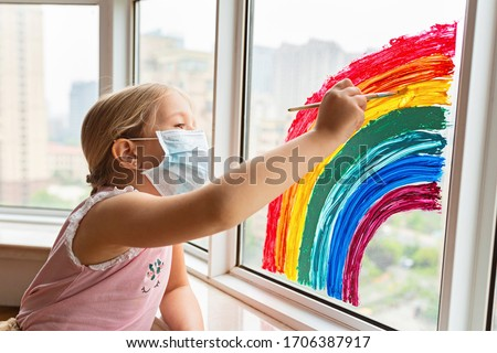 Kid painting rainbow during Covid-19 quarantine at home. Girl near window. Stay at home Social media campaign for coronavirus prevention, let's all be well, hope during coronavirus pandemic concept #1706387917