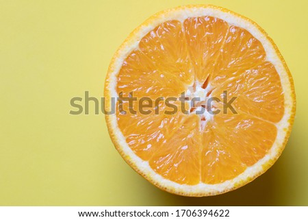 a fantastic minimal photograph of a sliced orange on a pastel yellow coloured background, studio shot