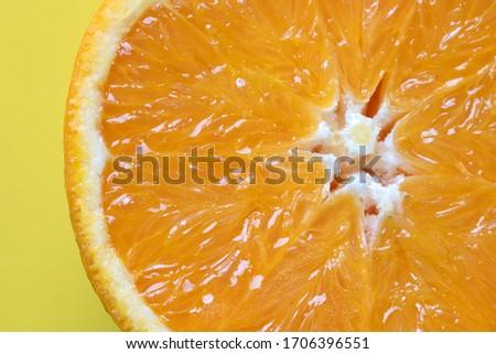 a fantastic minimal closeup photograph of a sliced orange on a pastel yellow coloured background, studio shot