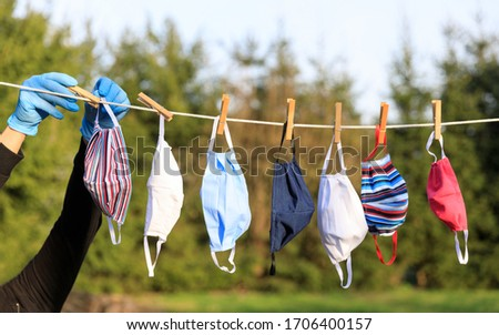 Drying mask hanging under the sun after use for disinfecting. Hygienic mask hanging on the rack outdoor after being washed for cleanness and hygiene during Covid-19 virus outbreak #1706400157