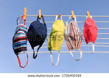 Drying mask hanging under the sun after use for disinfecting. Hygienic mask hanging on the rack outdoor after being washed for cleanness and hygiene during Covid-19 virus outbreak #1706400184