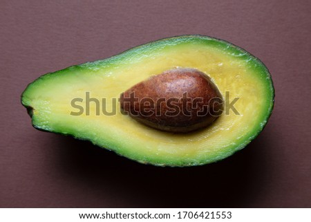 a closeup of a freshly sliced avocado on a brown coloured background, top view