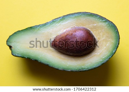 a closeup of a freshly sliced avocado on a yellow coloured background, top view