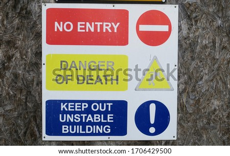 Vintage metal sign No entry Danger of Death and Keep Out Unstable building on chipboard background