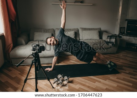 Young beautiful white man doing exercise on mat with camera. Shooting a video for the blog on videocamera. Online training. Sport in quarantine at home. #1706447623