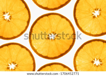 an interesting pattern of transparent orange slices against a bright white background
