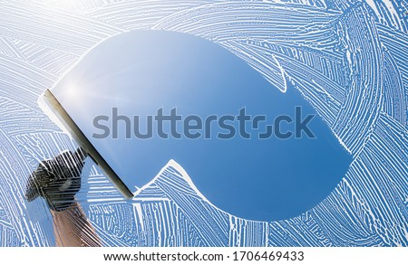 window cleaner cleaning window with squeegee and wiper on a sunny day Royalty-Free Stock Photo #1706469433