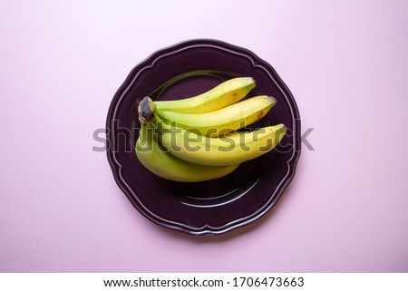 a stylish pastel coloured image of a bunch of bananas an a decorative purple plate with pink background, flat lay, top view