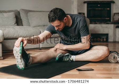 beautiful man doing stretching exercises on a mat. Sport in quarantine at home. Online lessons. Workout with an application on a smartphone. Royalty-Free Stock Photo #1706481274