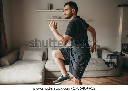 beautiful man doing exercises, running in room. Sport in quarantine at home, isolation, covid, virus. #1706484412