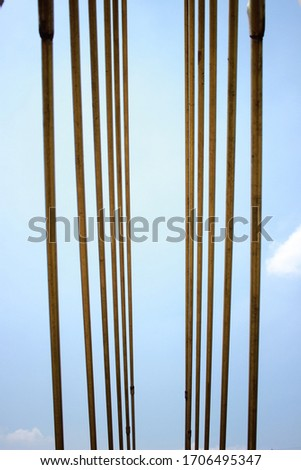 Abstract illustration photos. An iron buffer bridge crossing people with clear skies. photographed from the bottom. Selective Focus #1706495347