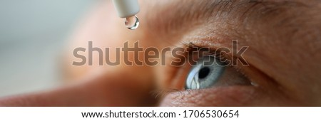 Man drops eye drops install lenses, moisturizing. Preservation and solution vision problems. Eye diseases are recognized. Drops before putting on lenses or before removing at end day Royalty-Free Stock Photo #1706530654