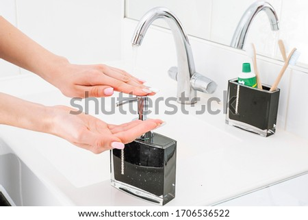 Hand washing with soap. Hand hygiene closeup. A woman washes her hands in the bathroom. Photo of hand disinfection. Antibacterial soap. Soap dish for liquid soap. Royalty-Free Stock Photo #1706536522