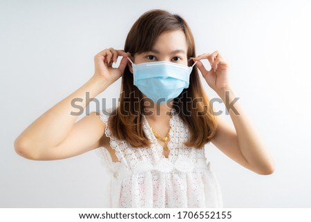 Close up portrait of young woman with medicine health care mask against white white background. CoronaVirus, Covid-19. Asian people #1706552155