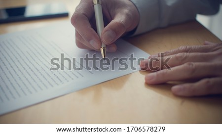 A person signing a document. Hand holding a pen and signing.