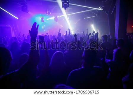 Kaunas, Lithuania- november, 2018: Rear view of crowd with arms outstretched at concert. silhouettes of concert crowd in front of bright stage lights. Crowd at music concert, audience raising hands up #1706586715