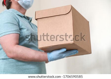 Parcel delivery with copy space. Courier in gloves and a mask with a box for a customer. A man with a parcel in his hands. #1706590585