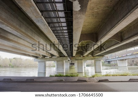 Bottom view of the prestressed concrete beams and piers of Pont d'Empalot, a girder bridge in Toulouse, France, crossing the River Garonne and supporting the six-lane express way of Toulouse ring road #1706645500