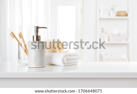 Soap dispenser, toothbrushes and white towel on bathroom counter interior #1706648071