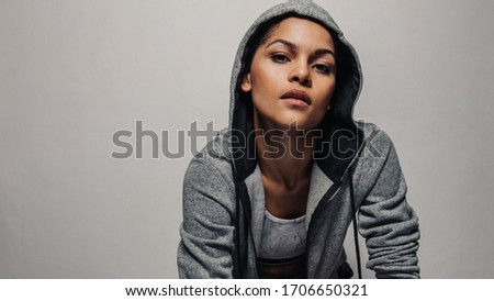 Fitness woman wearing a hoodie jacket staring at camera. Healthy female in sportswear against grey background. Royalty-Free Stock Photo #1706650321