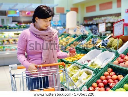 pretty caucasian woman choosing apple during shopping at fruit vegetable supermarket #170665220