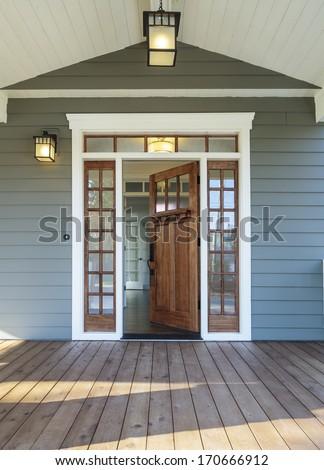 Vertical shot of wooden front door  of an upscale home with windows/Exterior shot of an open Wooden Front Door #170666912