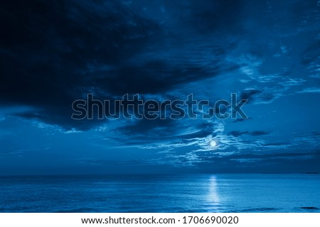 This photo illustration of a deep blue moonlit ocean and sky at night  would make a great travel background for any travel or vacation purpose.