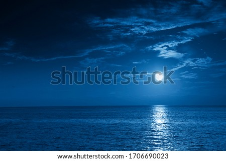 This photo illustration of a deep blue moonlit ocean and sky at night  would make a great travel background for any travel or vacation purpose. #1706690023