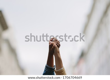 Black lives matter. Symbolic picture showing that we are stronger together. Two people holding hand and raising in unity. Symbol of unity and anti racism.  #1706704669