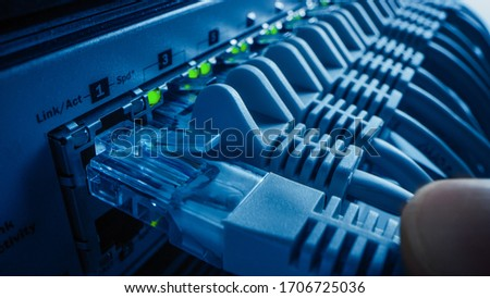 Close-up Macro Shot: Person Plugs in RJ45 Internet Connector into LAN Router Switch. Information Communication Network with Data Cable Being Connected to Port with Blinking Lights. Blue Background Royalty-Free Stock Photo #1706725036