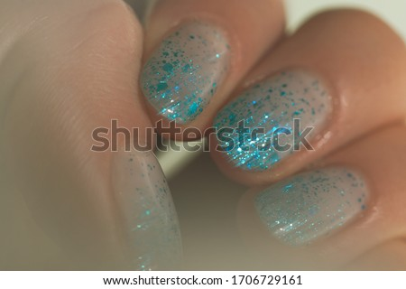 Soft female mood. Shiny glitter gradient nails design. Beautiful nail art with aquamarine tinsel. Closeup photo with soft grease effect #1706729161