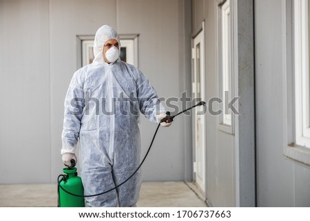 Man in virus protective suit and mask disinfecting buildings of coronavirus with the sprayer. Infection prevention and control of epidemic. World pandemic. #1706737663