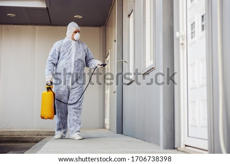 Man in virus protective suit and mask disinfecting buildings of coronavirus with the sprayer. Infection prevention and control of epidemic. World pandemic. Royalty-Free Stock Photo #1706738398