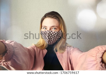 Woman wearing  handmade cloth cotton face mask at home. Protect against corona virus. Quarantine concept. Reusable face mask. #1706759617