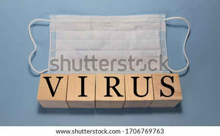 """wooden cubes with the text """"virus"""" and a medical white mask on a blue background, medicine concept #1706769763"""