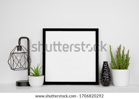 Mock up black square frame with home decor and potted plants. White shelf and wall. Copy space. Royalty-Free Stock Photo #1706820292