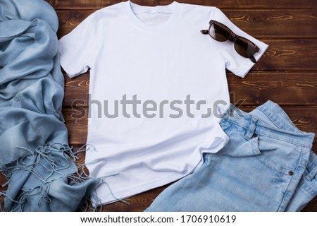 White women's cotton T-shirt mockup with blue jeans, sunglasses and turquoise scarf. Design t shirt template, tee print presentation mock up Royalty-Free Stock Photo #1706910619