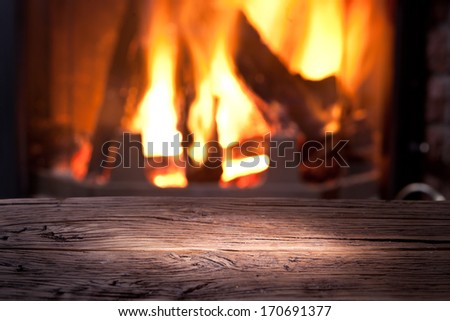 Old wooden table in front of the fireplace. Home background.